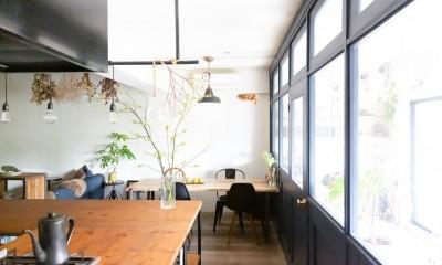 アイアンフレームのオリジナルキッチンと飛び床の土間の家 (壁一面の室内窓)
