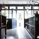 アイアンフレームのオリジナルキッチンと飛び床の土間の家の写真 大きな室内窓