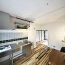 古い建物ならではの味わいを生かしながら、現代の暮らしに合わせたレトロモダンな空間への写真 ステンレスキッチンでスッキリとまとめたキッチンスペース