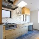 明るく楽しい色づかいの写真 タイル貼りの壁とオリジナル造作のキッチン