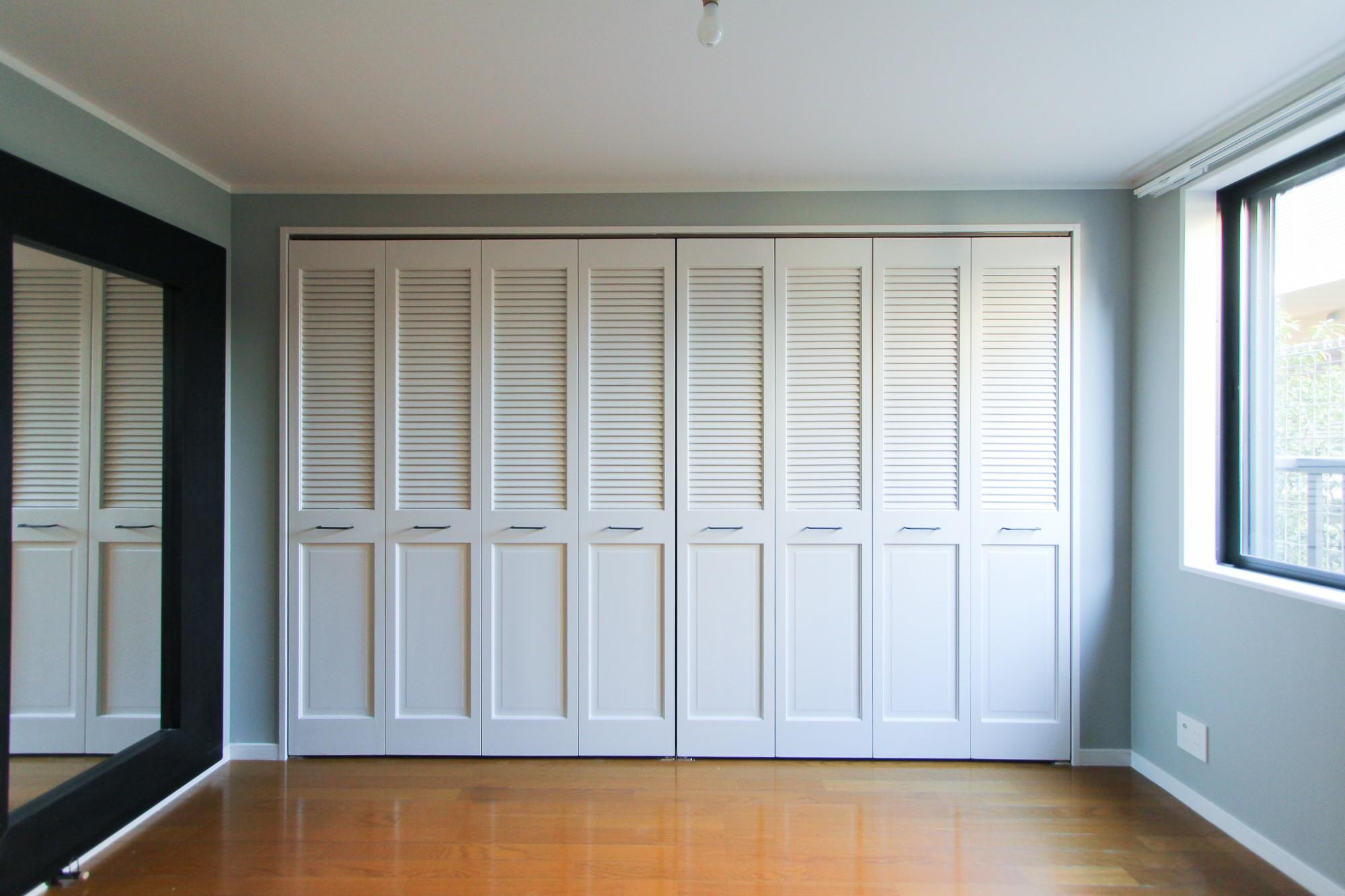 グレーの壁紙の寝室のクローゼットドア 明るく楽しい色づかい ベッドルーム事例 Suvaco スバコ