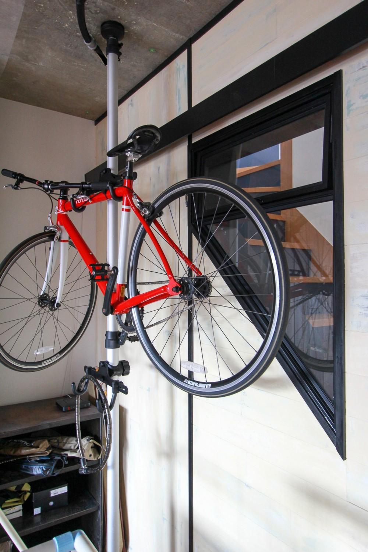 素材感で味付けしてよみがえるマンションリノベーション (自転車ポールと階段に合わせて斜めに開口した室内窓。)