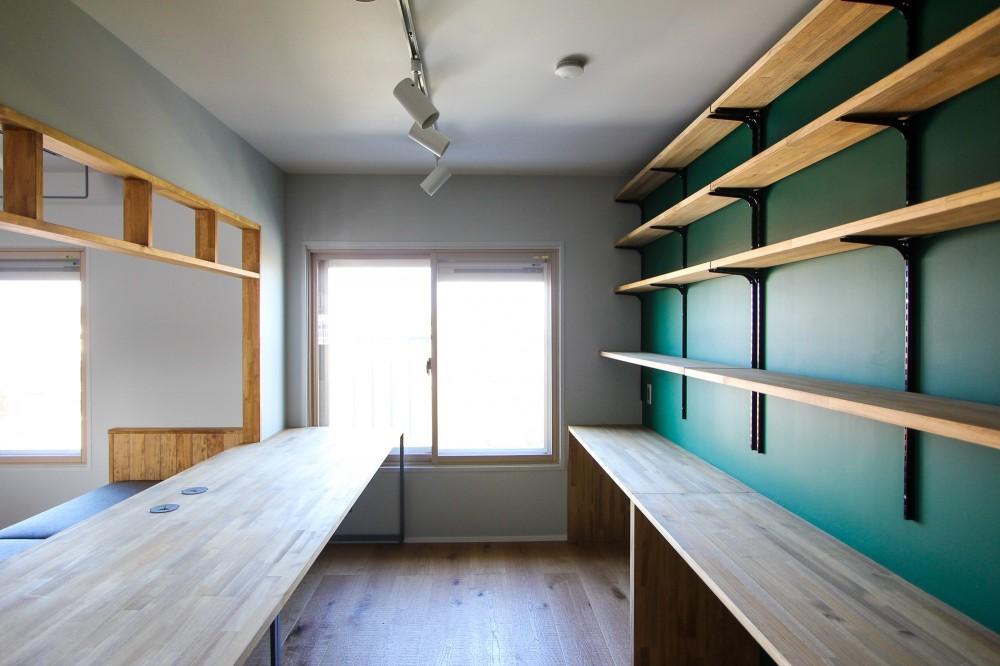 ふたりだけの特別なスペース (デスクと緑色の壁の壁面収納)