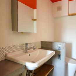 ふたりだけの特別なスペース (オレンジ色の天井とコンクリート天板の洗面室)