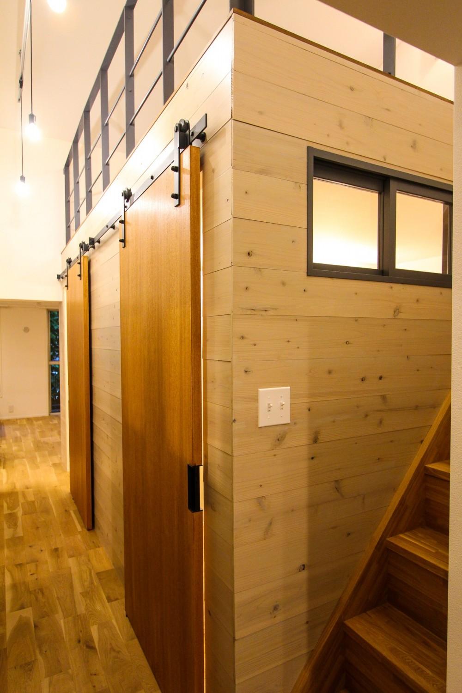 風の抜けるロフトのある家 (個室の引き戸とロフトへの階段)