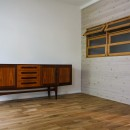 風の抜けるロフトのある家の写真 ビンテージ家具と室内窓のあるリビング