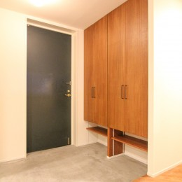 北欧ミッドセンチュリーの似合う家 (木製扉の下駄箱とモルタル仕上げの玄関)
