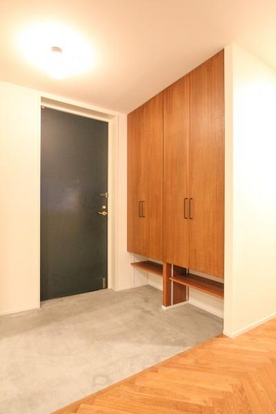 木製扉の下駄箱とモルタル仕上げの玄関 (北欧ミッドセンチュリーの似合う家)