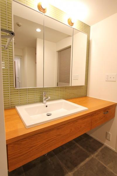 タイル貼りの壁と引き出しのある木製の洗面カウンター (北欧ミッドセンチュリーの似合う家)