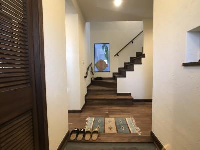 珪藻土の白い壁にウォールナットの床が映える玄関 (海の見える絶好のロケーションと無垢の木で「好き」をつめこんだこだわりの家)