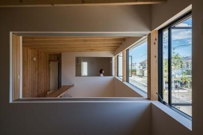 室内窓を通して対面する個室を眺める (いつでも空が見える吹き抜けと、公園のような庭のある家)