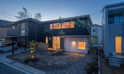 いつでも空が見える吹き抜けと、公園のような庭のある家 (温かな灯りが窓からこぼれる夕方の景色)