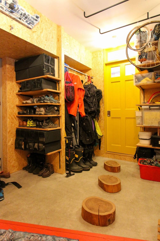 赤い床の山小屋ハウス (黄色い扉と丸太の置かれた玄関土間)