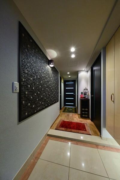 シックで高級感のある玄関 (こだわりの内装と付け梁で憧れの南国リゾートホテル風の住まいへ)