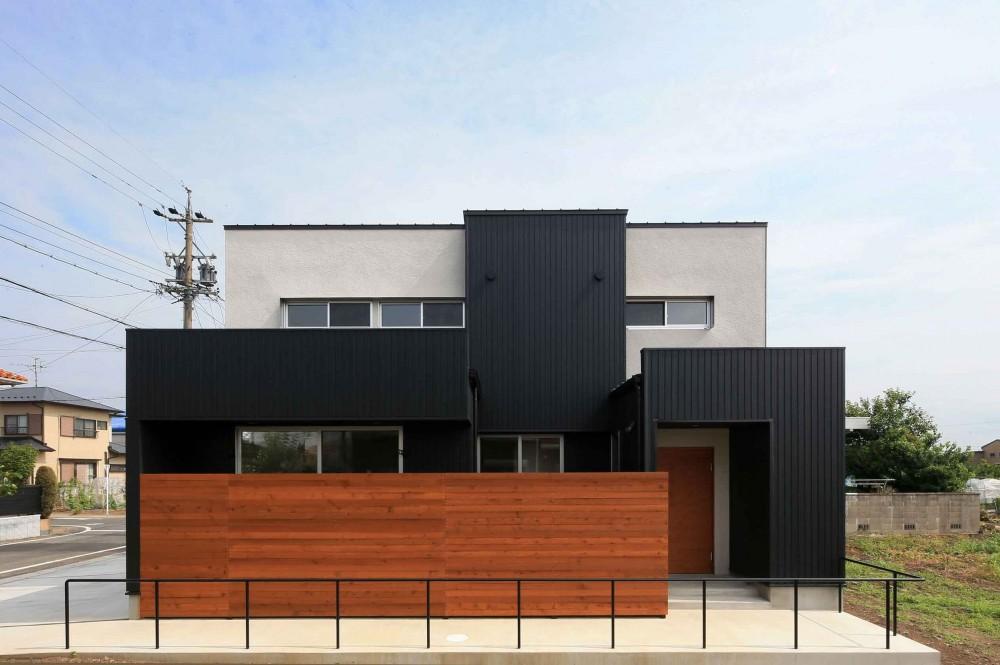アプローチと中庭に木塀が一体になる家。異素材の調和とプライバシーを重視した住まい。 (外観)