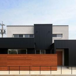 外観 (アプローチと中庭に木塀が一体になる家。異素材の調和とプライバシーを重視した住まい。)