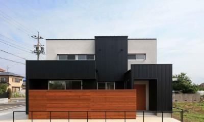 アプローチと中庭に木塀が一体になる家。異素材の調和とプライバシーを重視した住まい。