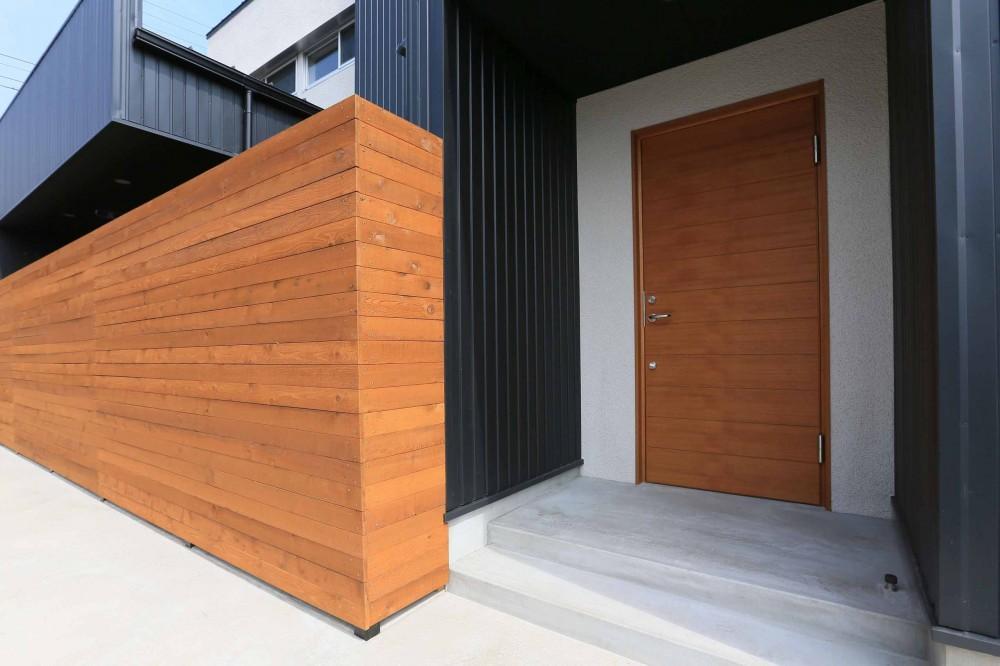 アプローチと中庭に木塀が一体になる家。異素材の調和とプライバシーを重視した住まい。 (ポーチ)