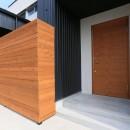 アプローチと中庭の木塀が一体になる家。異素材の調和とプライバシーを重視した住まい。の写真 ポーチ