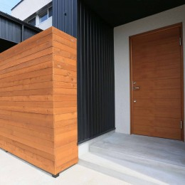 アプローチと中庭の木塀が一体になる家。異素材の調和とプライバシーを重視した住まい。 (ポーチ)