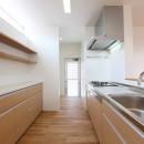 アプローチと中庭の木塀が一体になる家。異素材の調和とプライバシーを重視した住まい。の写真 キッチン