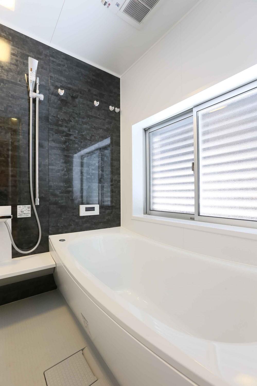 アプローチと中庭の木塀が一体になる家。異素材の調和とプライバシーを重視した住まい。 (浴室)