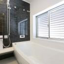 アプローチと中庭の木塀が一体になる家。異素材の調和とプライバシーを重視した住まい。の写真 浴室