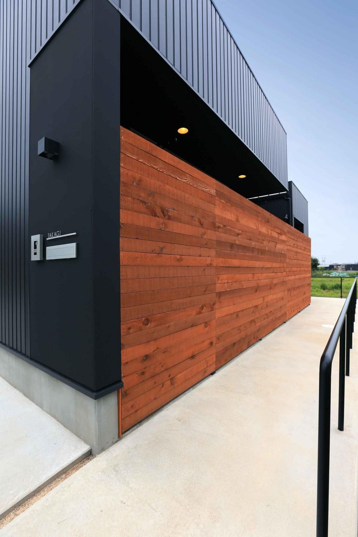 アプローチと中庭に木塀が一体になる家。異素材の調和とプライバシーを重視した住まい。 (アプローチ)