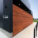 アプローチと中庭の木塀が一体になる家。異素材の調和とプライバシーを重視した住まい。の写真 アプローチ