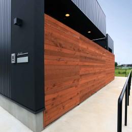 アプローチと中庭の木塀が一体になる家。異素材の調和とプライバシーを重視した住まい。