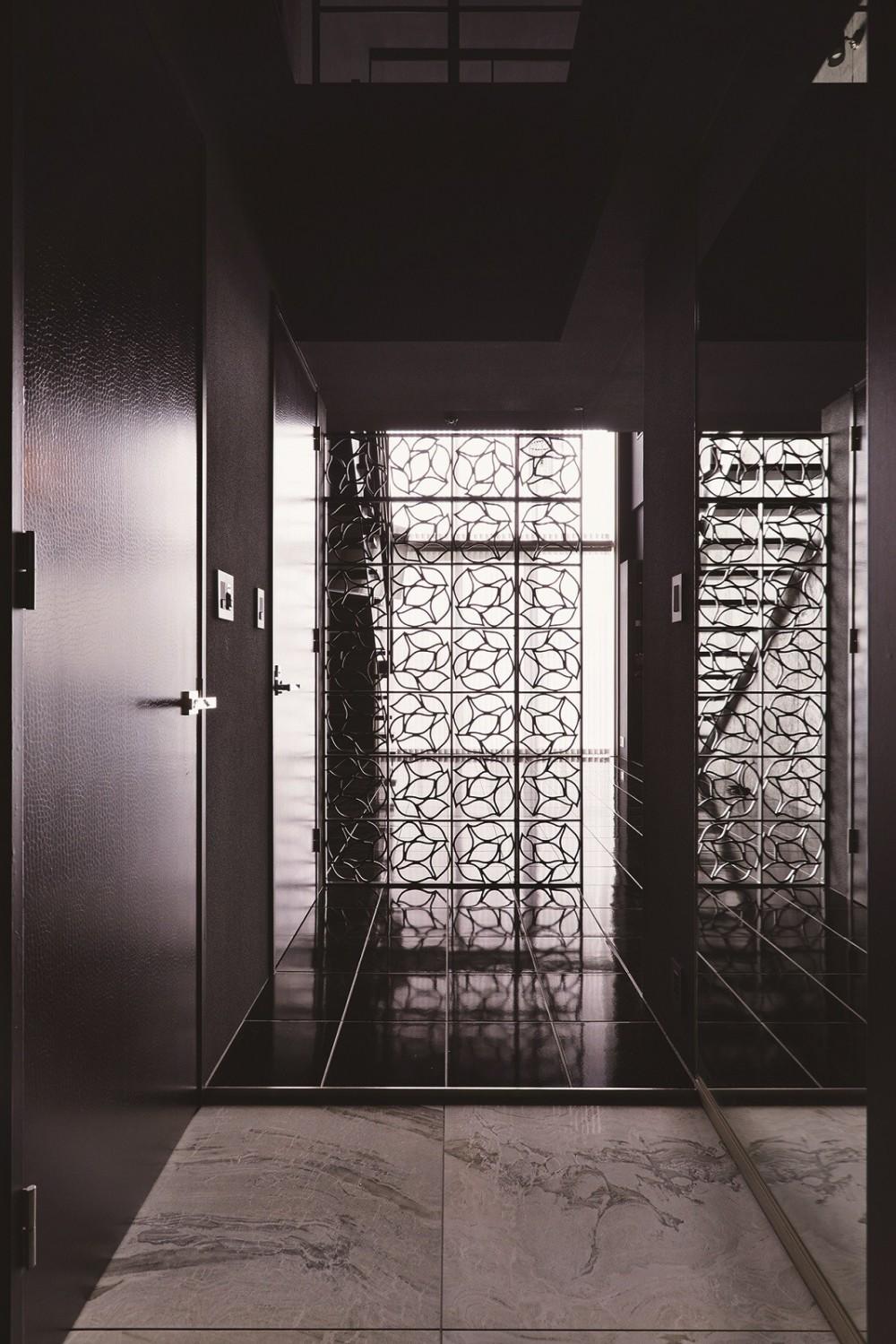 吹き抜け空間を中心としたフルリノベーション (黒で統一されている玄関)