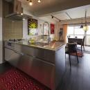 個性溢れる家具とアートが融合するリゾートスタイルのセカンドハウスの写真 アクセントタイルとオールステンレスが調和する海外風キッチン