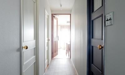 兵庫県S邸  − 北欧のヴィンテージ家具を素敵に魅せる家 − (廊下に並ぶ白と黒の扉)
