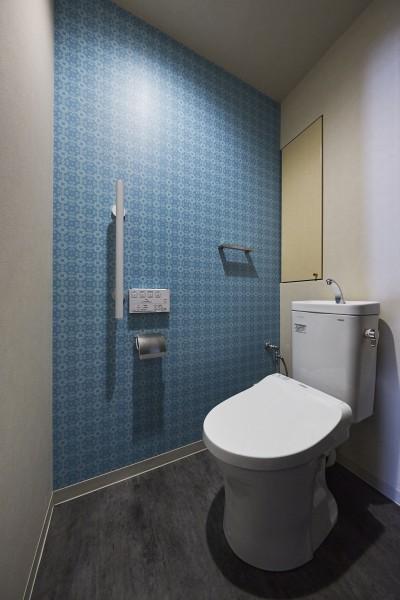 """ターコイズブルーのアクセントクロスでポップな空間 (造作棚でコレクションを効率良く収納。""""見せる収納""""が主役のお家)"""