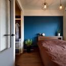 RC躯体の武骨な眺め 個性的なアメリカンモダン・インテリア<第34回「住まいのリフォームコンクール」作品部門 優秀賞 受賞>の写真 壁一面にブルーを塗装したカジュアルモダンな寝室