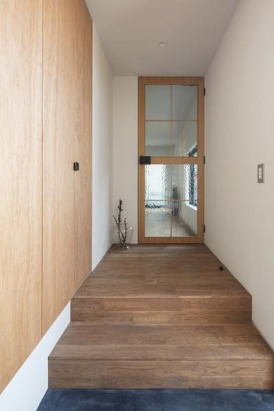 エントランスからリビング方向。アンティークガラスを嵌めた扉はリビングへの入口でもあり、小さな家の出口でもある。 (四つ角の家|家の中に4つの小さな家がある住宅【大阪府堺市】)