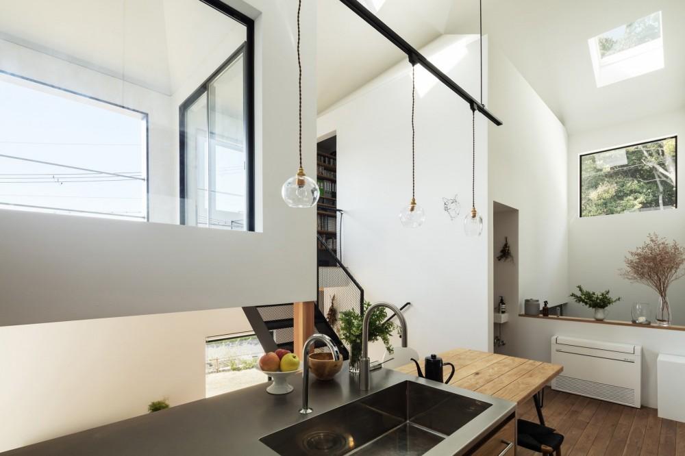 四つ角の家|家の中に4つの小さな家がある住宅【大阪府堺市】 (キッチンから水廻りを納めた小さな家を見る。窓には庭の芝生、雑木林の緑、空だけが映る。)