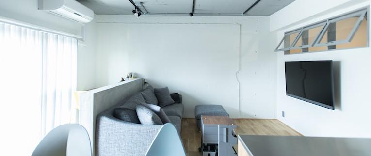 清潔感あふれる、コンパクトなシンプルルーム (腰壁を利用し、空間をゆるく区切ったリビング)