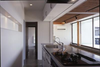 ストックと通路と一体化したキッチン (ビアンコネロ 英語教室を兼ねる子供と外を楽しむ家)