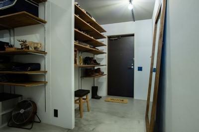 たくさんの収納棚を備えた広い玄関スペース (小上がりのベッドルームで光を取り入れるユニークなお部屋)