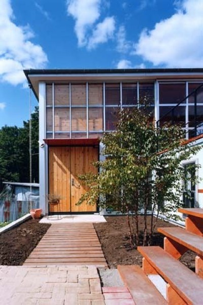 中庭から玄関を見る (二つの木箱 2世帯とアトリエをつなぐ巨大なデッキ)