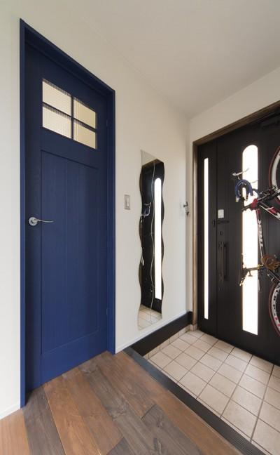 ブルーの造作扉が印象的な玄関 (限られた予算でイメージ通りの家)