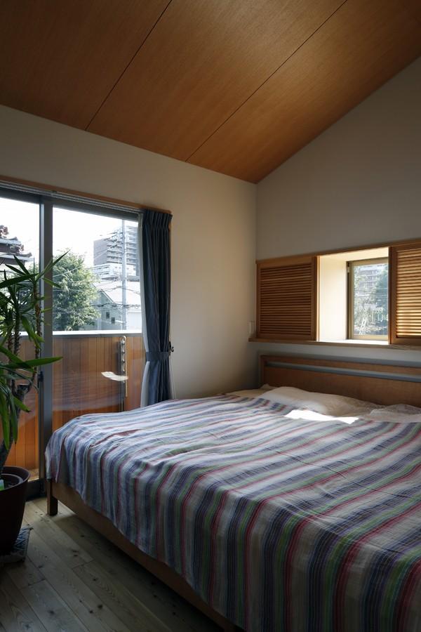 小さな吹抜けとペレットストーブの家 (寝室)