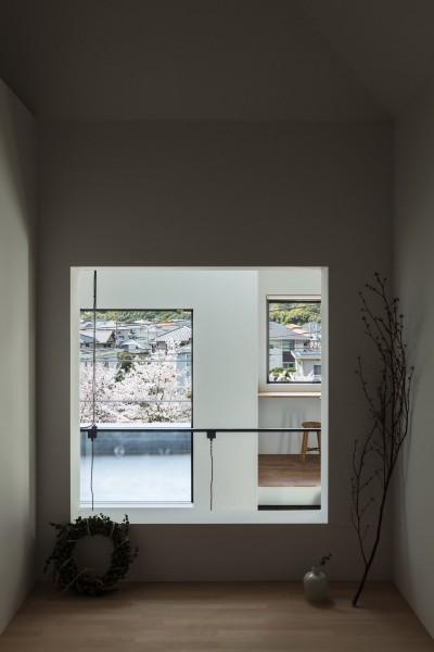 和室の窓から大きな家、テラス、桜並木を見通す。 (四つ角の家|家の中に4つの小さな家がある住宅【大阪府堺市】)
