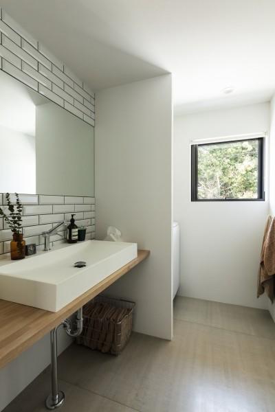 雑木林の緑を楽しめる洗面室・浴室。壁面はサブウェイタイル。 (四つ角の家|家の中に4つの小さな家がある住宅【大阪府堺市】)