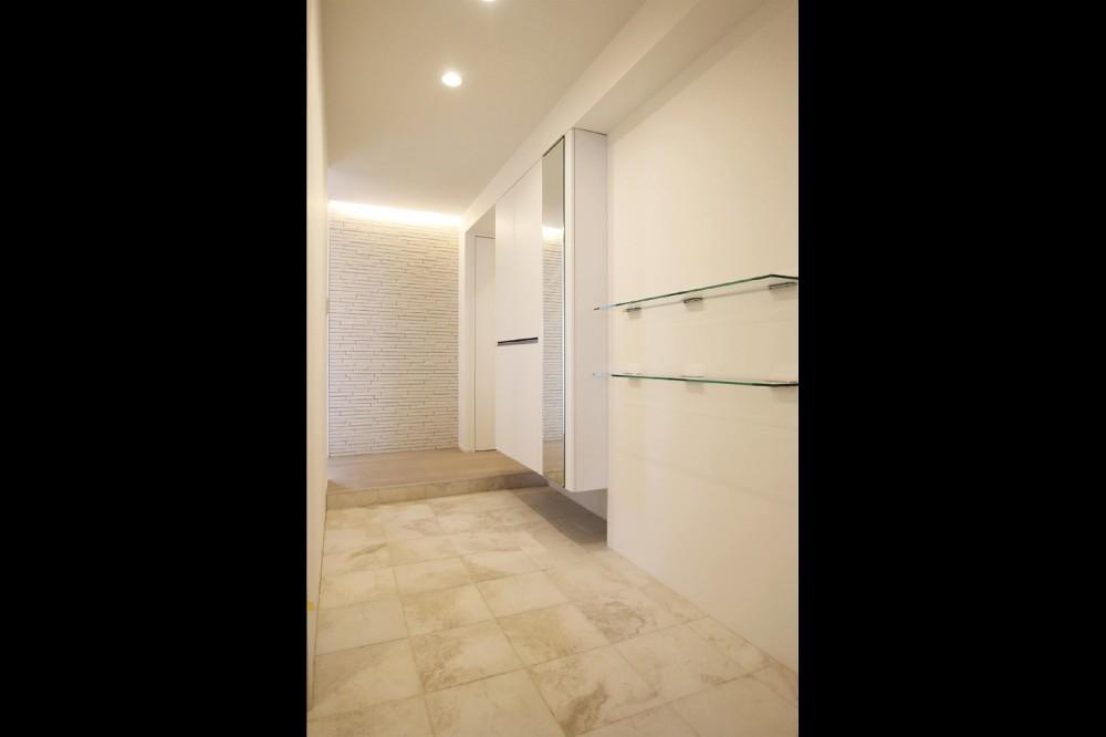 グレートーンの空間に明るい陽を入れ、間取りの中心にⅡ型キッチンを。 (玄関・ホール)