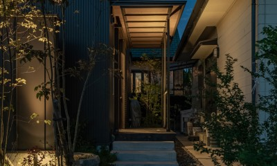 「垂坂山の家」デッキコートとつながる家 (玄関アプローチ・夕景)