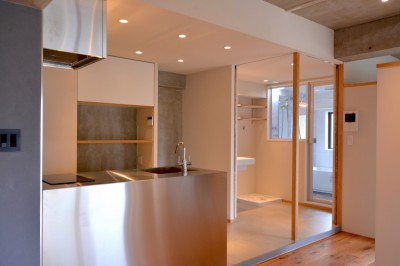 引き戸を開けるとキッチンと洗面室が伸びやかにつながります。 (調布市のWさんの家)