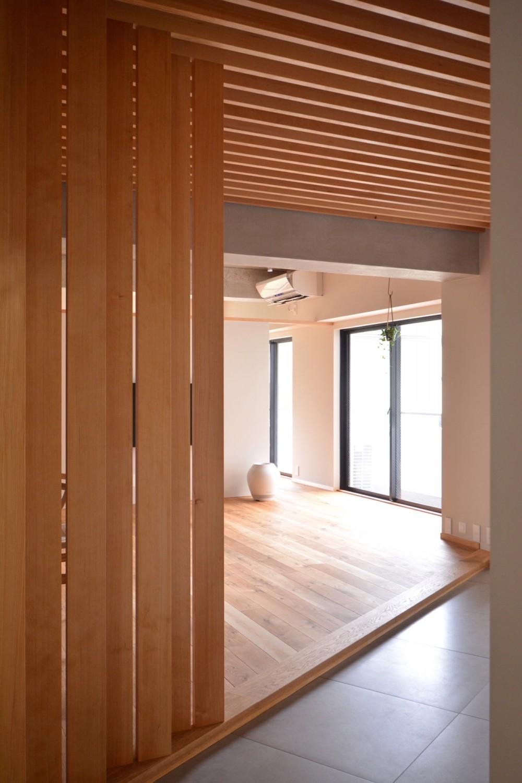 調布市のWさんの家 (玄関ドアを開けて中に入ると木製のルーバーが縦に並んでいます)