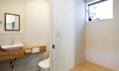 中庭のある無垢な珪藻土の家 – 共働き世帯の家事効率を練りに練ったプラン – (エントランスつながるヒノキの階段と横のお手洗い)